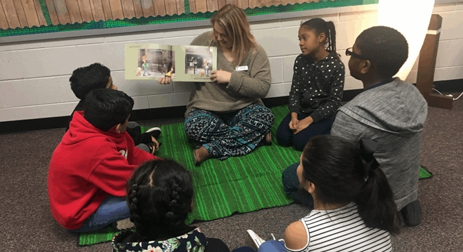 teacher sitting on the floor reading to kids
